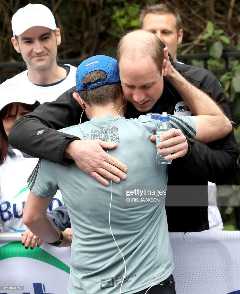 Britain's Prince William, Duke of Cambridge hugs a runner during the 2017 London Marathon in London on April 23, 2017. / AFP PHOTO / POOL / Chris Jackson