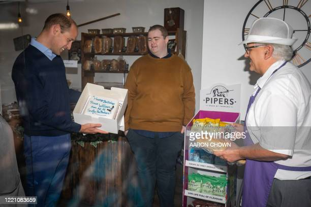Britain's Prince William, Duke of Cambridge, is presented by shop owner Paul Brandon with a birthday cake, who will be 38 on June 21, during a visit...