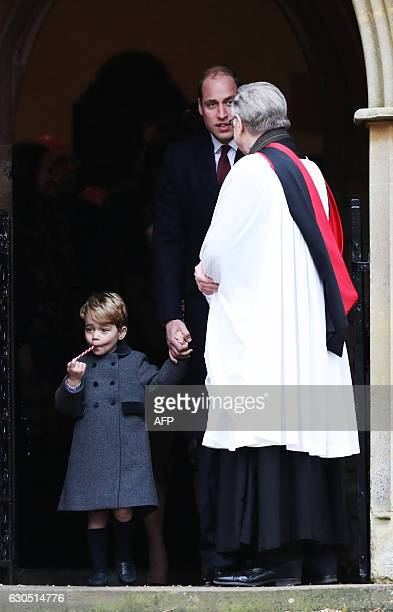 Britain's Prince William Duke of Cambridge leads his son Prince George out of church after attending a Christmas Day service at St Mark's Church in...