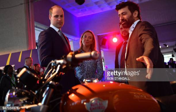 Britain's Prince William Duke of Cambridge looks at a display of Royal Enfield motorcycles during a 'Welcome to the UK' reception on the opening day...
