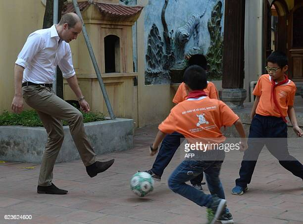 TOPSHOT Britain's Prince William Duke of Cambridge plays football with pupils as he visits a local primary school in the old quarters of Hanoi on...