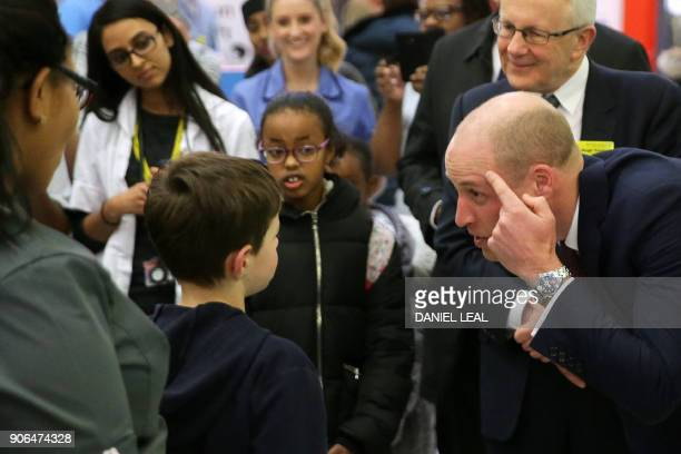 Britain's Prince William Duke of Cambridge points to an old scar as he meets a young patient during a visit to Evelina London Children's Hospital in...