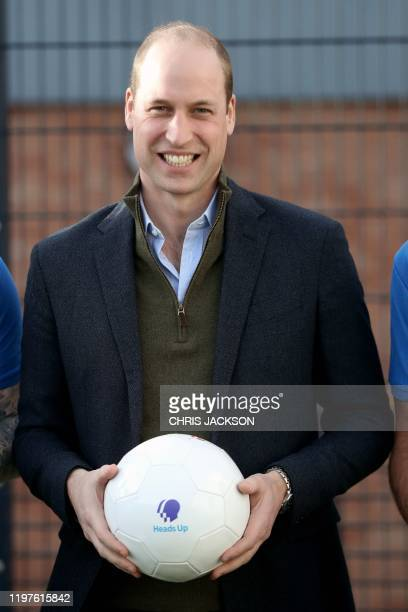 Britain's Prince William, Duke of Cambridge poses with footballers during a visit to Everton Football Club's official charity, Everton in the...