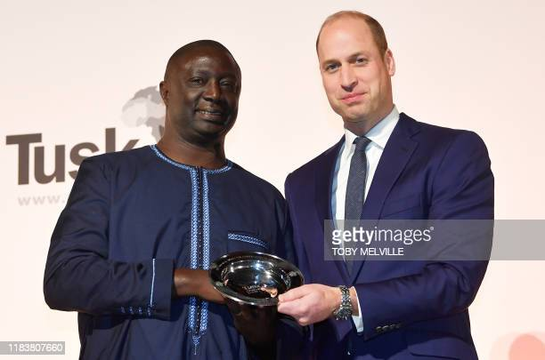 Britain's Prince William Duke of Cambridge poses with the Winner of the 2019 Tusk Award for Conservation in Africa Tomas Diagne during The Tusk...