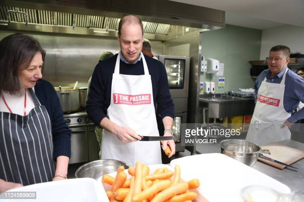 Britain's Prince William Duke of Cambridge reacts as he helps prepare food during his visit to homelessness charity The Passage in London on February...