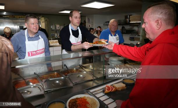 Britain's Prince William, Duke of Cambridge reacts as he helps serve food during his visit to homelessness charity The Passage in London on February...
