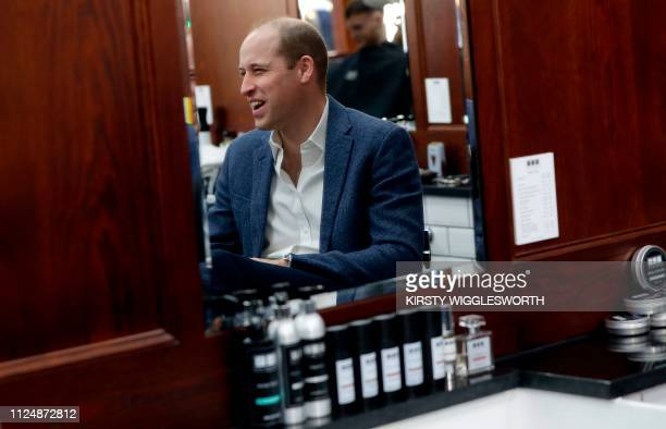 Britain's Prince William Duke of Cambridge reacts as he is pictured reflected in a mirror during a visit to Pall Mall Barbers in London on February...
