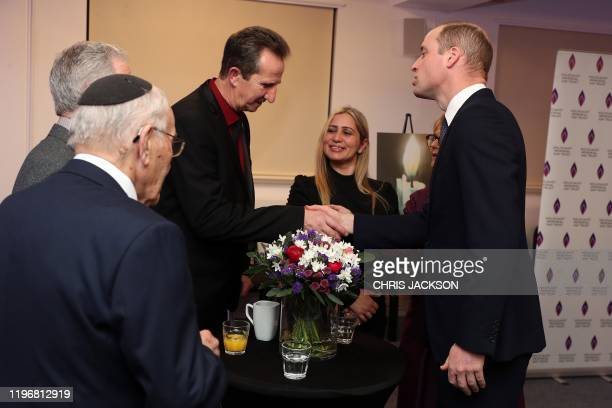 Britain's Prince William Duke of Cambridge shakes hands with Dzemal Paratusic survivor of the Genocide in Bosnia after the UK Holocaust Memorial Day...