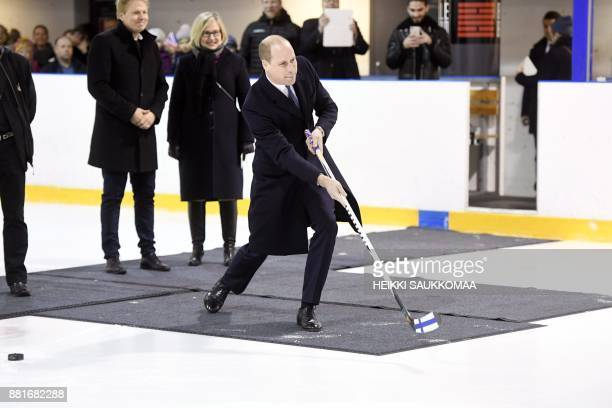 Britain's Prince William Duke of Cambridge shoots the puck during a meeting with members of the Icehearts ice hockey club on November 29 2017 in...