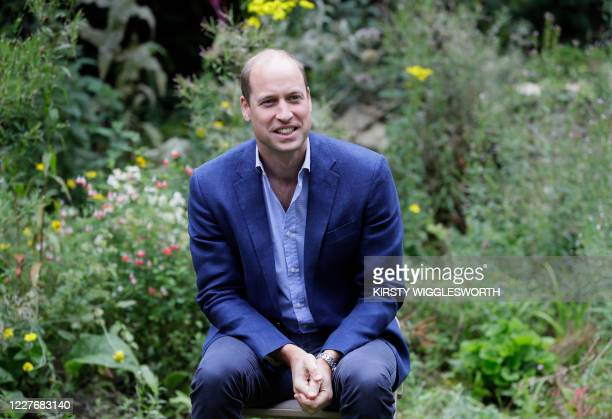Britain's Prince William, Duke of Cambridge socially distances as he speaks with service users during a visit to the Garden House of the Light...