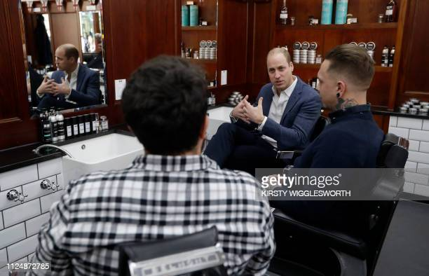 Britain's Prince William Duke of Cambridge speaks speaks to Dean Hamilton and Paul Richardson during a visit to Pall Mall Barbers in London on...