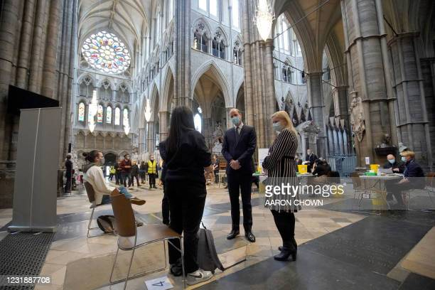 Britain's Prince William, Duke of Cambridge speaks to health workers as he visits the coronavirus vaccination centre at Westminster Abbey, central...
