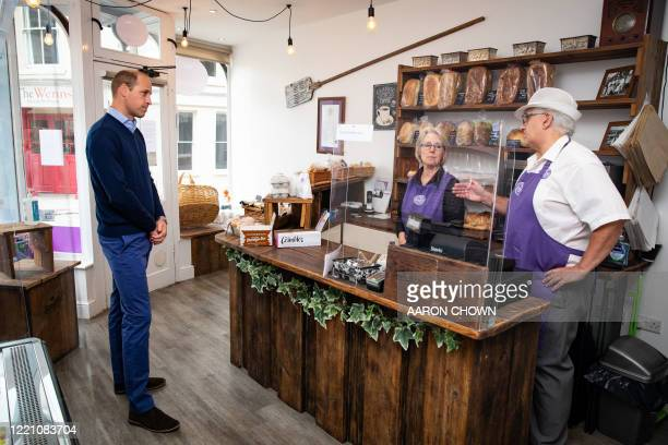 Britain's Prince William Duke of Cambridge speaks to owners Paul and Teresa Brandon durign a visit to Smiths the Bakers in the High Street in King's...