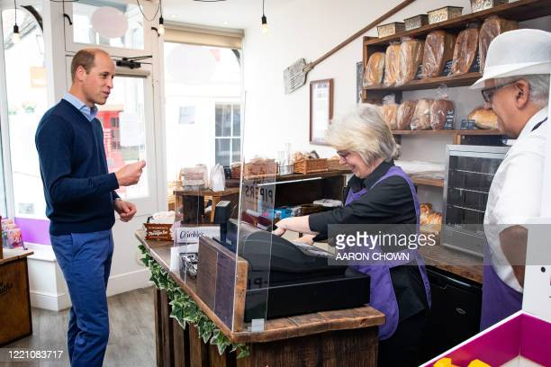 Britain's Prince William, Duke of Cambridge, speaks to owners Paul and Teresa Brandon during a visit to Smiths the Bakers in the High Street in...