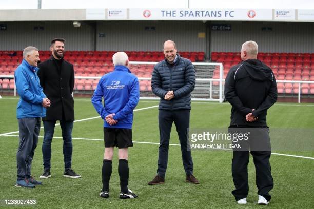 Britain's Prince William, Duke of Cambridge speaks with David MacPhee and footballer Steven Thompson during a visit to Spartans FC's Ainslie Park...