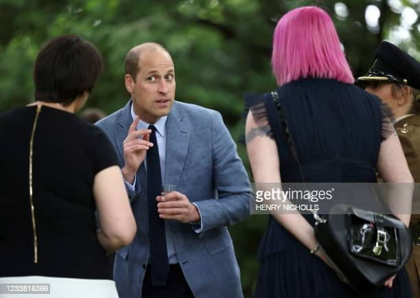 Britain's Prince William, Duke of Cambridge speaks with guests as he hosts a NHS Big Tea in the gardens of Buckingham Palace in London on July 5 to...