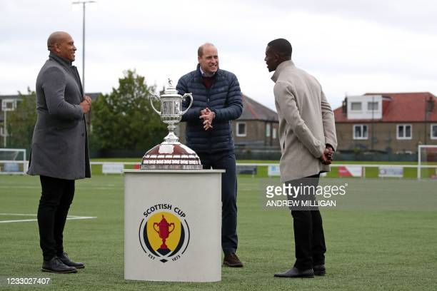 Britain's Prince William, Duke of Cambridge stands by the Scottish Cup with Scottish former professional footballer Chris Iwelumo and English...