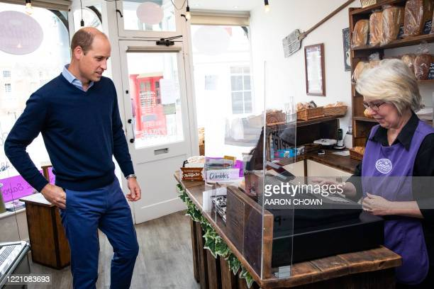 Britain's Prince William Duke of Cambridge uses contactless payment to pay owner Teresa Brandon for his purchases during a visit to Smiths the Bakers...