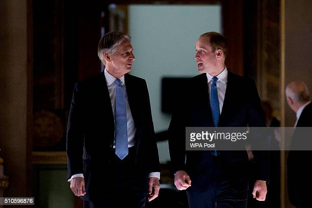 Britain's Prince William Duke of Cambridge walks with Foreign Secretary Philip Hammond as he visits the Foreign and Commonwealth Office on February...