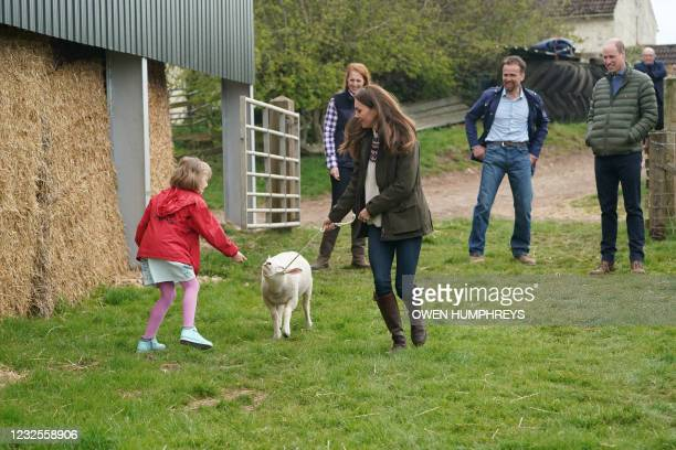 Britain's Prince William, Duke of Cambridge, watches as his wife Britain's Catherine, Duchess of Cambridge walks with nine-year-old Clover , a...