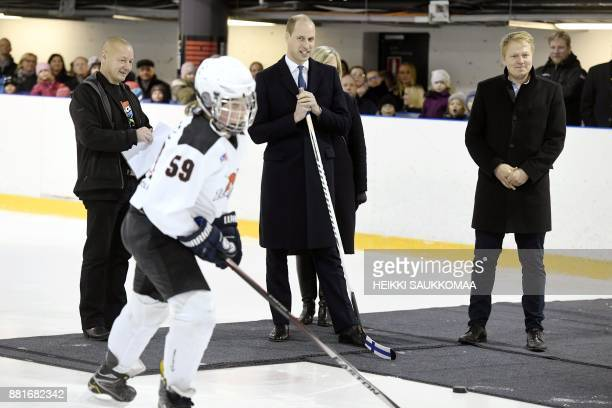Britain's Prince William Duke of Cambridge watches young players showing their skills during a meeting with members of the Icehearts ice hockey club...