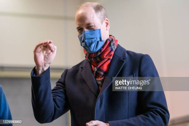Britain's Prince William, Duke of Cambridge, wearing a protective face covering to combat the spread of the coronavirus, speaks with staff during a...
