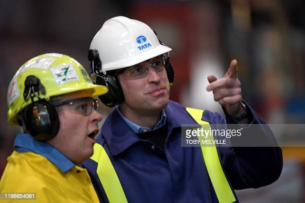 Britain's Prince William Duke of Cambridge wears a hard hat and protective clothes as he speaks with Works Manager Carl Banfield during his visit to...