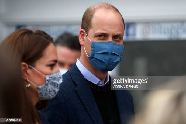 Britain's Prince William, Duke of Cambridge, wears a protective face covering to combat the spread of the coronavirus, as he and Britain's Catherine,...