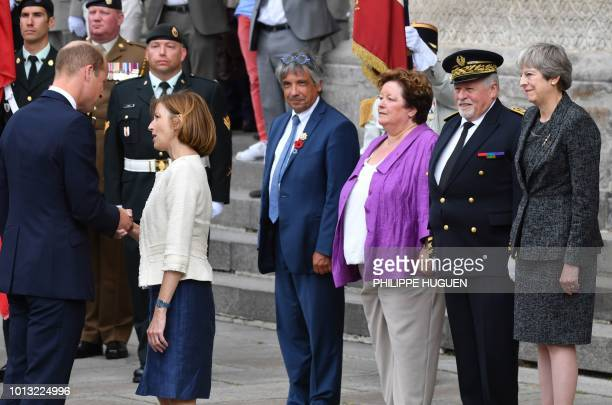 Britain's Prince William is watched by Britain's Prime Minister Theresa May as he shakes hands with French Defence Minister Florence Parly in Amiens...