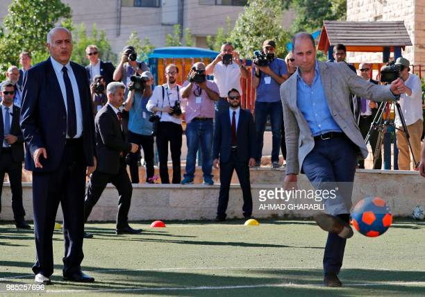 TOPSHOT Britain's Prince William kicks a ball next to the head of the Palestinian Football Federation Jibril Rajoub in the West Bank city of Ramallah...
