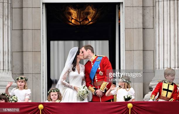 Britain's Prince William kisses his wife Kate Duchess of Cambridge on the balcony of Buckingham Palace after the wedding service on April 29 in...