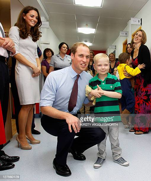 Britain's Prince William meets patient Ellis Andrews as he and his wife Catherine the Duchess of Cambridge open a children's cancer unit at the Royal...