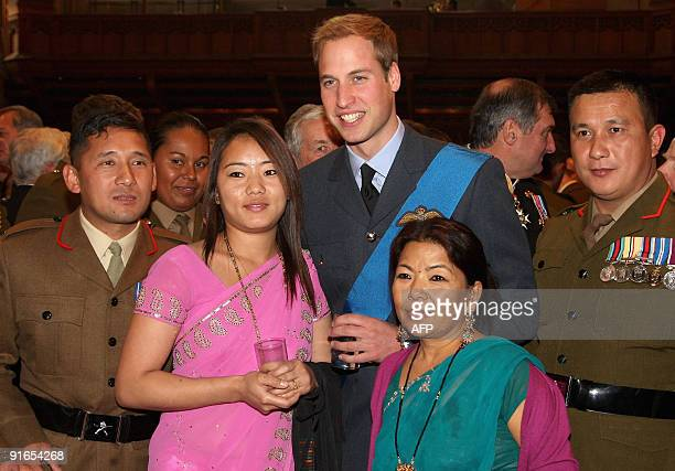 Britain's Prince William poses for photographs with soldiers during a reception at the Guildhall in London following a service of commemoration to...