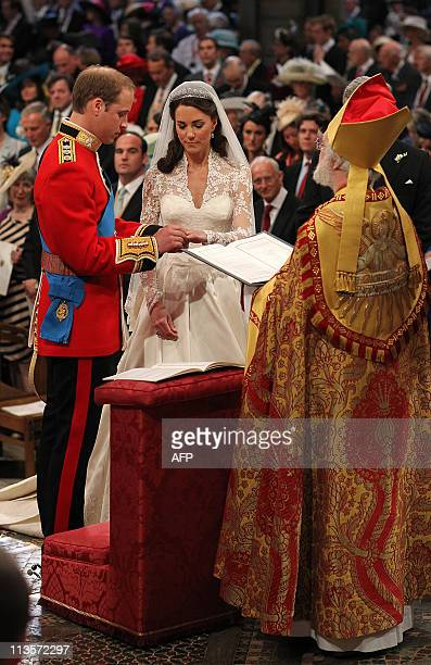 Britain's Prince William puts a ring fashioned from a nugget of Welsh gold on ther finger of Kate Duchess of Cambridge in front of the Archbishop of...