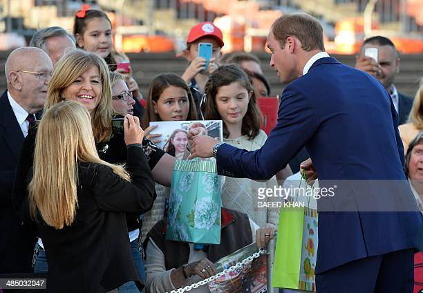 Britain's Prince William receives gifts for his son Prince George from the crowd after a reception at Sydney's iconic landmark Opera House on April...