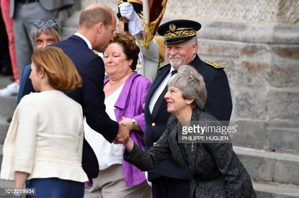 Britain's Prince William shakes hands with Britain's Prime Minister Theresa May in Amiens northern France on August 8 as he arrives to attend a...