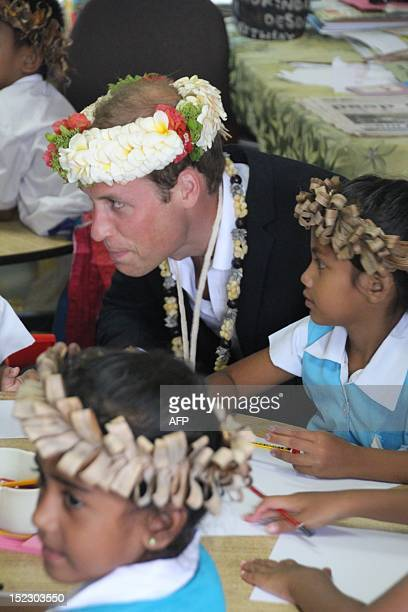 Britain's Prince William speaks to students as he visits the Nauti Primary School, the main government primary school in Tuvalu during a visit with...