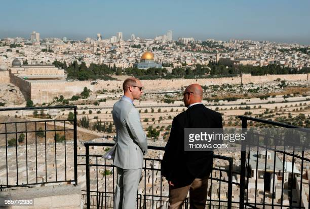 Britain's Prince William talks to a guide in Jerusalem's Mount of Olives overlooking the Old City with the golden dome of the Dome of the Rock mosque...