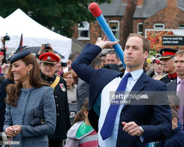Britain's Prince William throws a foam javelin as Catherine Duchess of Cambridge smiles as she stands at his side while they join in with a...