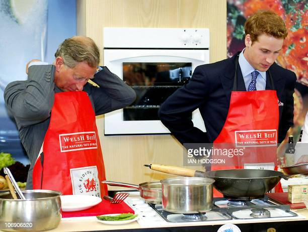 Britain's Prince William tries his hand at cooking with his father Prince Charles of Wales during a visit to the Anglesey Agricultural centre in...