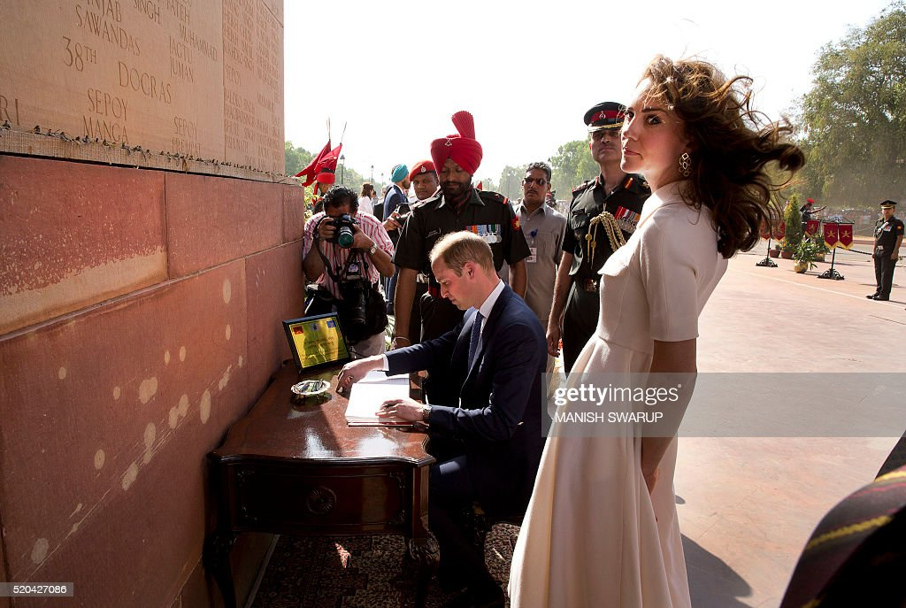 Britain's Prince William,Duke of Cambridge(C)signs the visitor's book as his wife Catherine Duchess of Cambridge(R)looks on after paying tribute at the India Gate war memorial, in the memory of the soldiers from Indian regiments who served in World War I, in New Delhi on April 11, 2016. / AFP / POOL / Manish Swarup