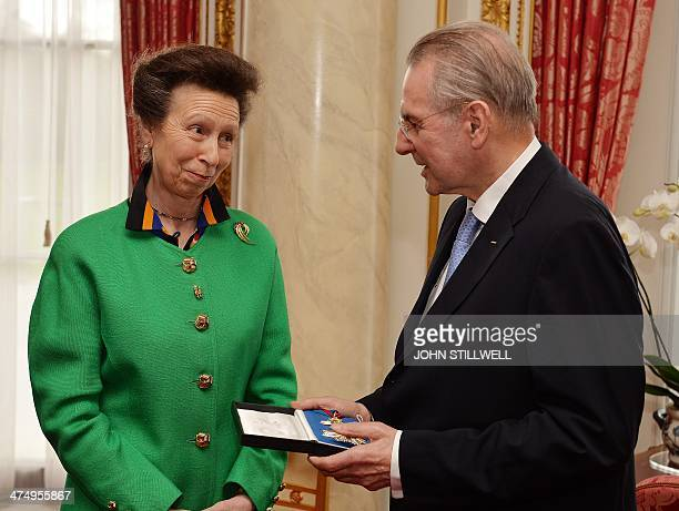 Britain's Princess Anne presents former International Olympic Committee President Jacques Rogge with his insignia of KCMG during a private...