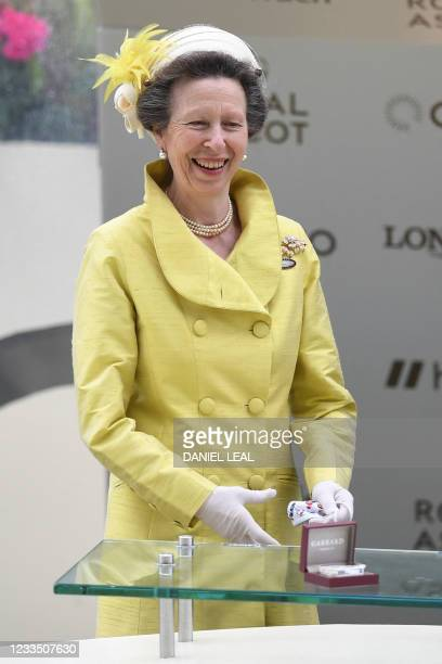 Britain's Princess Anne, Princess Royal smiles as jockey Joe Fanning poses with the trophy after riding Subjectivist to victory in the Gold Cup on...