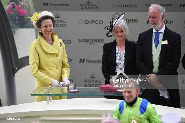 Britain's Princess Anne, Princess Royal smiles as she stands with owner James Walker as jockey Joe Fanning poses with the trophy after riding...