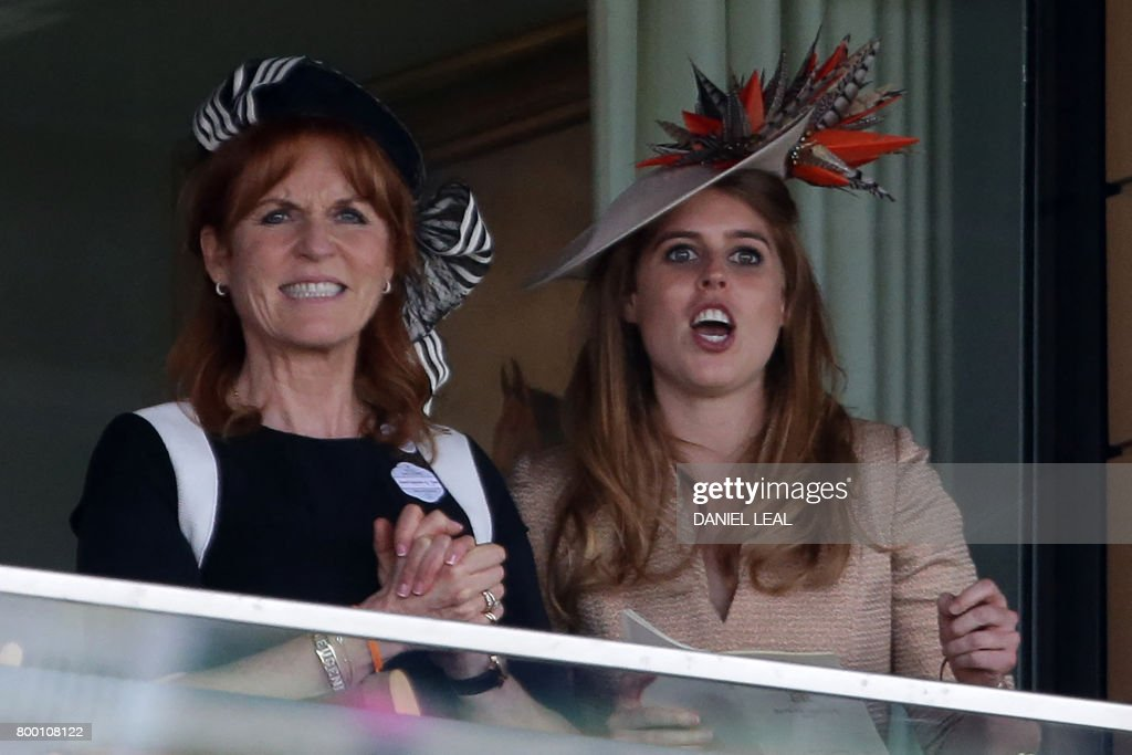 Britain's Princess Beatrice of York (R) and Sarah, Duchess of York react as they watch the King Edward VII Stakes on the fourth day of the Royal Ascot horse racing meet, in Ascot, west of London, on June 23, 2017. The five-day meeting is one of the highlights of the horse racing calendar. Horse racing has been held at the famous Berkshire course since 1711 and tradition is a hallmark of the meeting. Top hats and tails remain compulsory in parts of the course while a daily procession of horse-drawn carriages brings the Queen to the course. / AFP PHOTO / Daniel LEAL