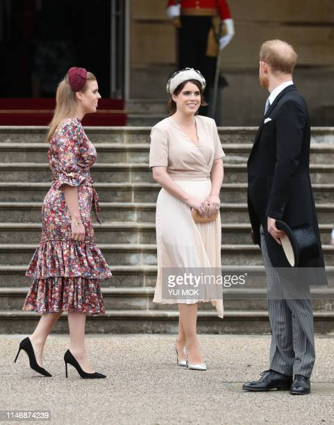 Britain's Princess Beatrice of York Britain's Princess Eugenie of York and Britain's Prince Harry Duke of Sussex chat at the Queen's Garden Party in...