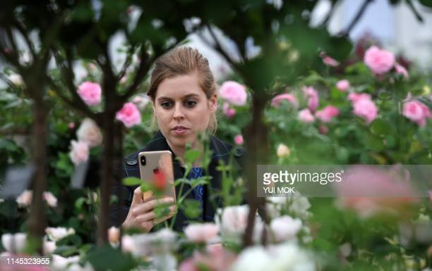 Britain's Princess Beatrice of York uses a mobile phone as she visits the 2019 RHS Chelsea Flower Show in London on May 20 2019 The Chelsea flower...