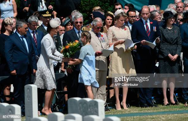 Britain's Princess Catherine Duchess of Cambridge receives a bouquet of flowers as Zonnebeke Mayor Dirk Sioen Vice Admiral Sir Timothy Laurence...