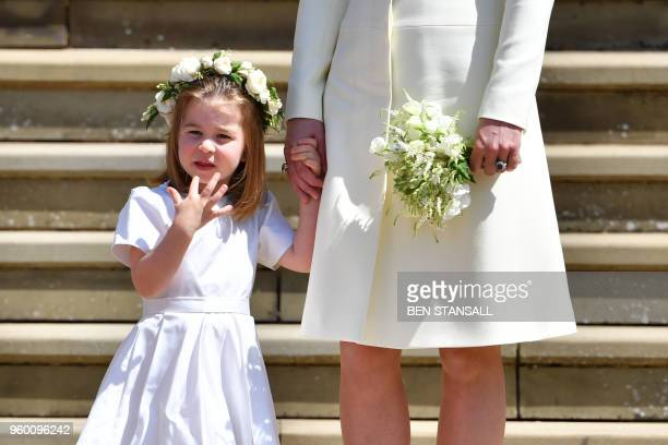 Britain's Princess Charlotte holds the hand of her mother Britain's Catherine Duchess of Cambridge after attending the wedding ceremony of Britain's...