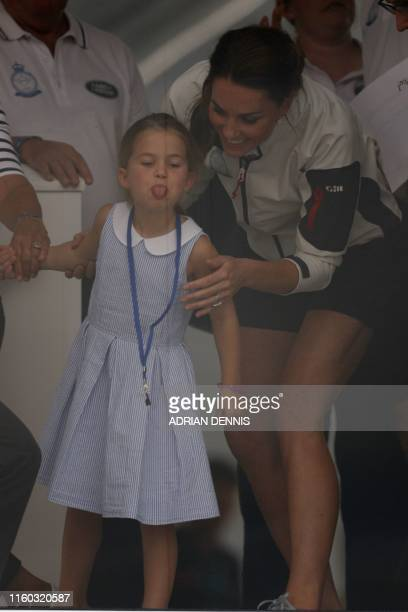 Britain's Princess Charlotte of Cambridge reacts with her mother Britain's Catherine Duchess of Cambridge prior to the presentation ceremony...